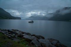 Pouco barco em um lago um o dia nebuloso do mistério no fiorde do geiranger de Noruega Fotografia de Stock Royalty Free