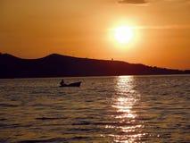 Pouco barco no por do sol dourado Foto de Stock Royalty Free