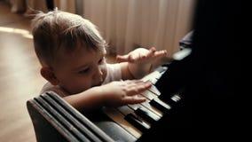 Pouco bebê bonito com sorriso em sua batida da cara em chaves do piano no movimento lento video estoque