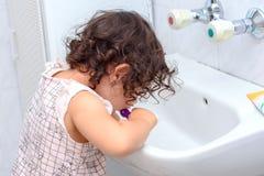 Pouco bebê bonito que limpa seus dentes com a escova de dentes no banheiro imagens de stock royalty free