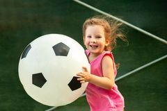 Pouco bebê corre com uma bola de futebol enorme fotografia de stock