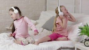 Pouco bebê da criança que escuta a música com fones de ouvido video estoque