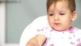 Pouco bebê mastiga vegetais A mamã alimenta uma criança pequena com uma colher de vegetais para o almoço
