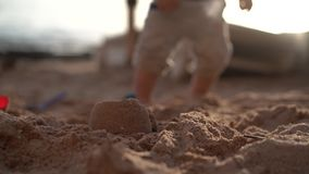 Pouco bebê na praia e na cubeta vermelha no movimento lento filme