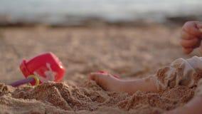 Pouco bebê na praia e na cubeta vermelha no movimento lento vídeos de arquivo