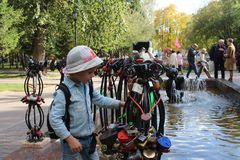Pouco bebê que anda considerando as decorações nos trilhos decorativos da fonte no primeiro quadrado em Novosibirsk imagens de stock royalty free