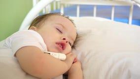 Pouco bebê que dorme com o termômetro sob seu braço na divisão de hospital na cama branca Medidas doentes da temperatura da crian filme