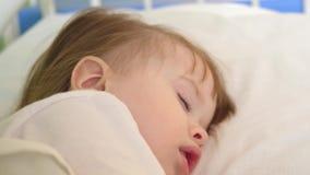 Pouco bebê que dorme na divisão de hospital no roupa de cama branco Tratamento das crianças no ajuste do hospital A criança doent filme