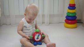 Pouco bebê que joga com blocos pequenos coloridos de um construtor na sala no assoalho Criança que joga com colorido video estoque
