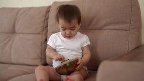 Pouco bebê que senta-se no sofá e que joga um instrumento musical Kalimba video estoque