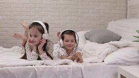 Pouco beb? da crian?a que escuta a m?sica com fones de ouvido vídeos de arquivo