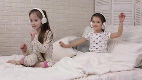 Pouco beb? da crian?a que escuta a m?sica com fones de ouvido video estoque