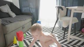 Pouco beb? que joga com blocos pequenos coloridos de um construtor na sala no assoalho Crian?a que joga com colorido vídeos de arquivo