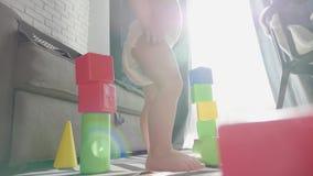 Pouco beb? que joga com blocos pequenos coloridos de um construtor na sala no assoalho Crian?a que joga com colorido filme