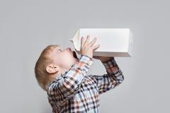 Pouco bebidas louras do menino de um grande pacote branco Fundo claro imagem de stock royalty free