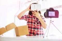Pouco blogger moderno que mostra a seus vidros novos da realidade virtual seus seguidores imagem de stock