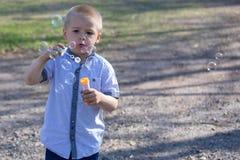 Pouco bolhas de sopro do menino bonito no parque foto de stock royalty free
