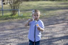 Pouco bolhas de sopro do menino bonito no parque imagens de stock