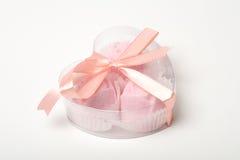 Pouco bolos cor-de-rosa em um coração deu forma à caixa sobre o branco Fotografia de Stock