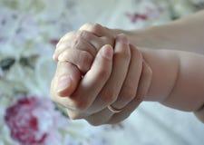 Pouco braço do bebê em uma mão fêmea Tema da maternidade e da infância, proteção da criança fotografia de stock