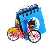 Pouco caderno azul ao lado de que é uma bicicleta pequena Imagem de Stock Royalty Free