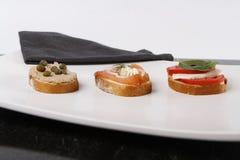 Pouco canapes com atum e alcaparra, tomate e mozarella, salmões e cebolas imagem de stock royalty free