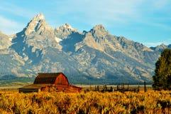 Pouco celeiro do registro dentro com montanhas como um contexto Fotos de Stock Royalty Free