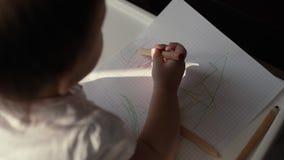 Pouco criança bonito da menina tira um lápis no fim do papel acima Tiro da parte traseira video estoque