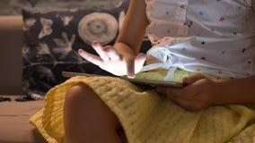 Pouco criança bonito que joga jogos na tabuleta e que senta-se no sofá na casa moderna, criança no conceito da casa, dentro video estoque