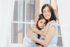 Pouco criança fêmea senta-se perto de sua mãe, sente o apoio e o amor de seu mum, levanta junto contra o fundo do peitoril da jan imagem de stock
