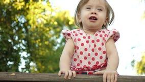 Pouco criança feliz que joga no banco no parque do verão A menina está sorrindo video estoque