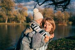 Pouco criança que abraça sua mamã A família que tem o divertimento no parque do outono fora, abraçando, rir, relaxando, aprecia a foto de stock royalty free