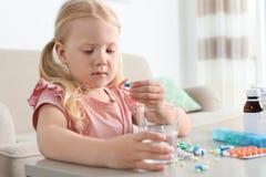 Pouco criança que toma o comprimido na tabela Perigo da intoxica??o do medicamento foto de stock royalty free