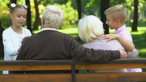 Pouco crianças bonitos que falam felizmente com as avós que sentam-se no banco no parque filme