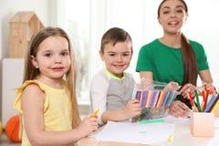 Pouco crianças com o desenho do professor de jardim de infância na tabela Aprendizagem e jogo imagem de stock
