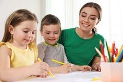 Pouco crianças com o desenho do professor de jardim de infância na tabela Aprendizagem e jogo fotos de stock