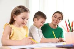 Pouco crianças com o desenho do professor de jardim de infância na tabela Aprendizagem e jogo fotos de stock royalty free
