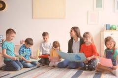 Pouco crianças com o professor na sala de aula na escola fotos de stock royalty free