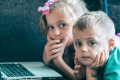Pouco crianças que olham desenhos animados em um portátil fotografia de stock royalty free