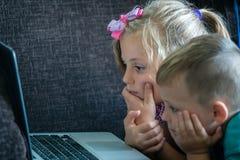 Pouco crianças que olham desenhos animados em um portátil imagens de stock royalty free