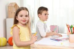 Pouco crianças que tiram na tabela Aprendizagem e jogo fotografia de stock royalty free