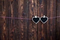 Pouco dois corações em uma corda pendura em uma corda cor-de-rosa em um fundo de madeira Fotografia de Stock Royalty Free