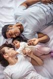 Pouco filha que toca na cara da sua mãe ao descansar na cama fotos de stock