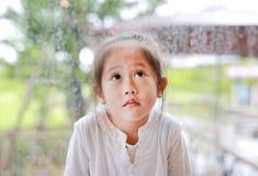 Pouco gesto asiático da menina da criança com cara calma e vista acima contra a janela de vidro com gota da água no dia chuvoso foto de stock