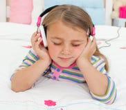 Pouco gril que escuta a música com auscultadores foto de stock royalty free