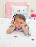 Pouco gril que escuta a música que encontra-se em sua cama fotos de stock royalty free