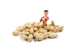 Pouco homem do amendoim entre amendoins Fotos de Stock