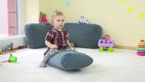 Pouco jogo feliz da menina com o descanso azul no brinquedo da sala de criança 4K vídeos de arquivo