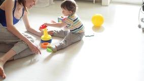 Pouco jogos do bebê no assoalho branco com mamã filme