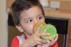 Pouco leite bebendo do beb? em sua garrafa verde foto de stock royalty free